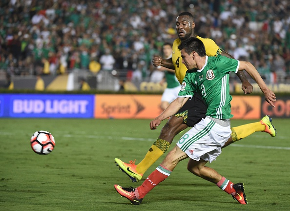 Mexico's Hirving Lozano (foreground) strikes the ball next to Jamaica's Westley Morgan during the Copa America Centenario football tournament in Pasadena, California, United States, on June 9, 2016. / AFP / Mark Ralston
