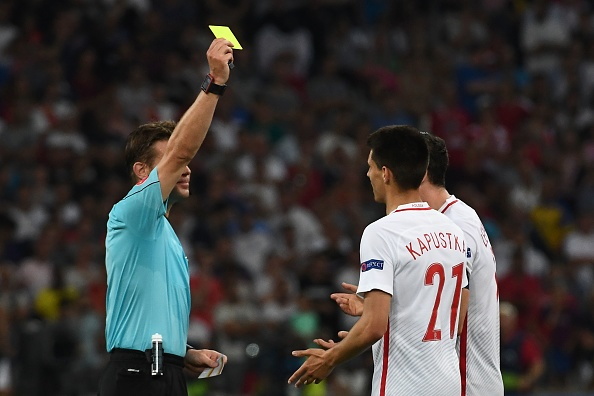 Poland's midfielder Bartosz Kapustka (R) receives a yellow card from German referee Felix Brych (L) during the Euro 2016 quarter-final football match between Poland and Portugal at the Stade Velodrome in Marseille on June 30, 2016. / AFP / ANNE-CHRISTINE POUJOULAT (Photo credit should read ANNE-CHRISTINE POUJOULAT/AFP/Getty Images)